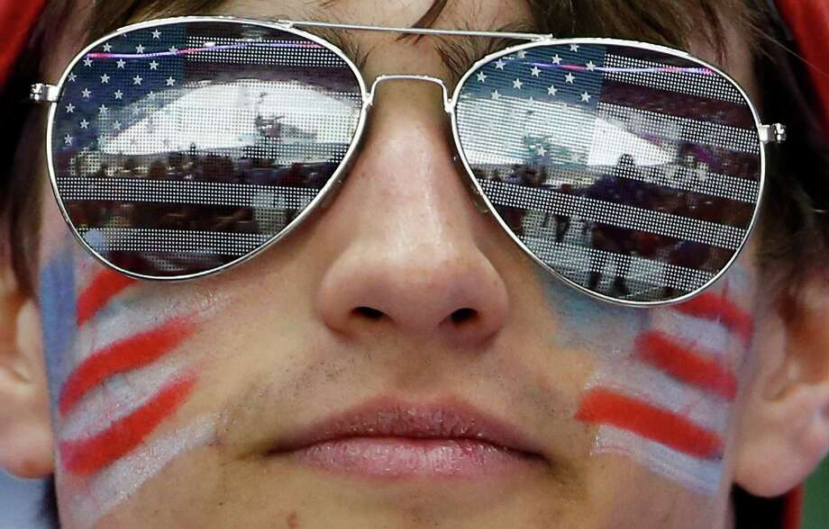 A U.S. hockey fan watches the USA and Russia men's hockey teams warm up before playing in a men's ice hockey game at the 2014 Winter Olympics, Saturday, Feb. 15, 2014, in Sochi, Russia. Photo: Julio Cortez, AP / AP