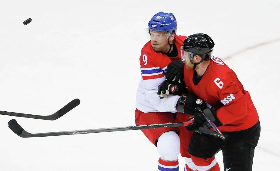 Czech Republic forward Milan Michalek and Switzerland defenseman Yannick Weber vie for the puck at mid ice in the third period of a men's ice hockey game at the 2014 Winter Olympics, Saturday, Feb. 15, 2014, in Sochi, Russia. Photo: Petr David Josek, AP / AP