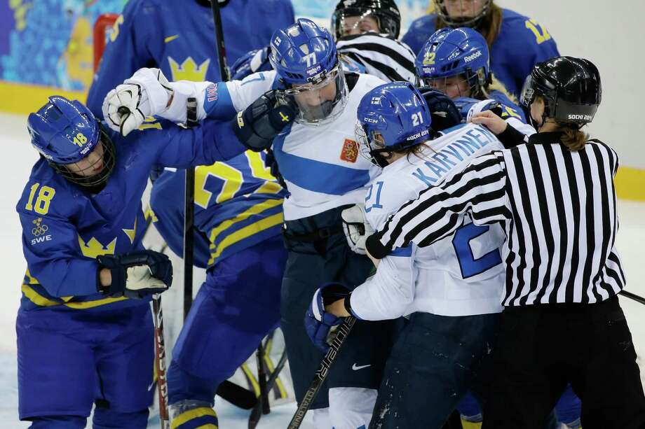 Members of Team Sweden and Team Finland mix it up during the 2014 Winter Olympics women's quarterfinal ice hockey game at Shayba Arena, Saturday, Feb. 15, 2014, in Sochi, Russia. Photo: Matt Slocum, AP / AP