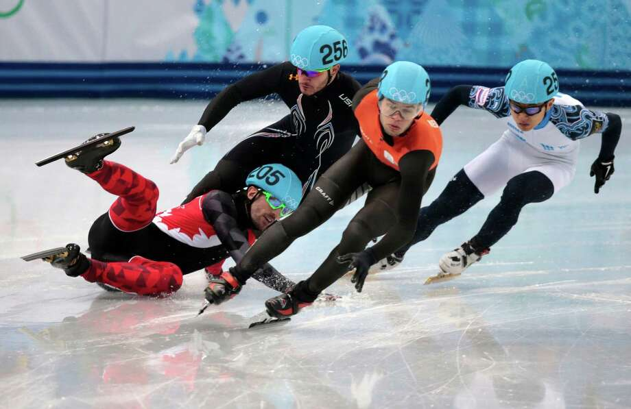 Charles Hamelin of Canada, left, crashes out with Eduardo Alvarez of the United States, second from left, as they compete with Sjinkie Knegt of Netherlands, second from right, and Victor An of Russia in a men's 1000m short track speedskating quarterfinal at the Iceberg Skating Palace during the 2014 Winter Olympics, Saturday, Feb. 15, 2014, in Sochi, Russia. Photo: Ivan Sekretarev, AP / AP2014