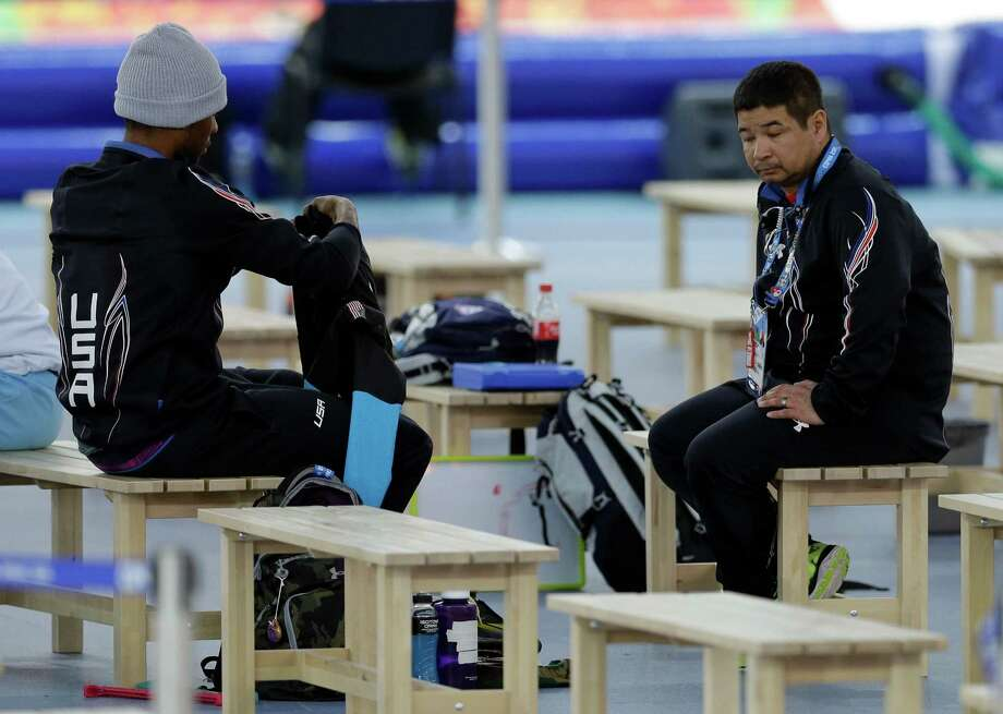Coach Ryan Shimabukuro waits as Shani Davis of the U.S. packs his belongings after the the men's 1,500-meter speedskating race at the Adler Arena Skating Center during the 2014 Winter Olympics in in Sochi, Russia, Saturday, Feb. 15, 2014. Photo: Patrick Semansky, AP / AP2014