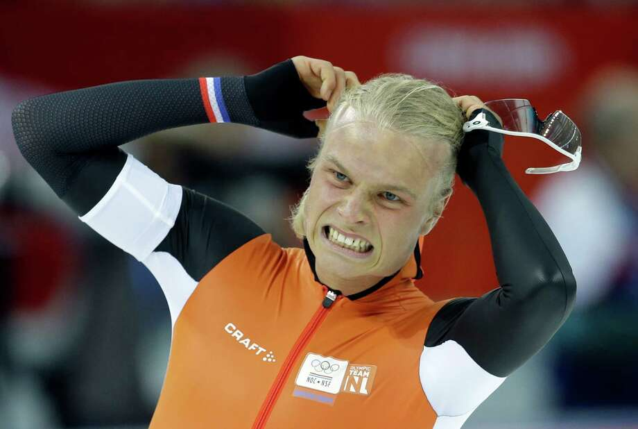 Silver medalist Koen Verweij of the Netherlands grabs his hair when the race was declared a tie with gold medalist Poland's Zbigniew Brodka  in the men's 1,500-meter speedskating race at the Adler Arena Skating Center during the 2014 Winter Olympics in Sochi, Russia, Saturday, Feb. 15, 2014. Verweij later was later declared silver, losing by three thousandth of a second. Photo: Patrick Semansky, AP / AP