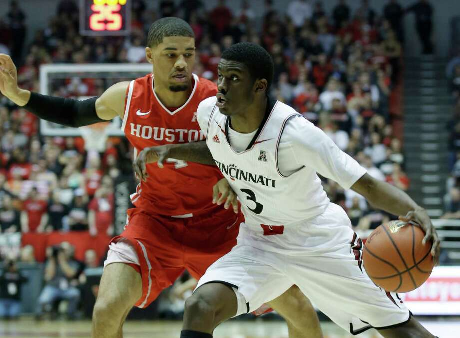 Cincinnati forward Shaquille Thomas (3) drives against Houston guard LeRon Barnes in the first half of an NCAA college basketball game, Saturday, Feb. 15, 2014, in Cincinnati. (AP Photo/Al Behrman) Photo: Al Behrman, Associated Press / AP