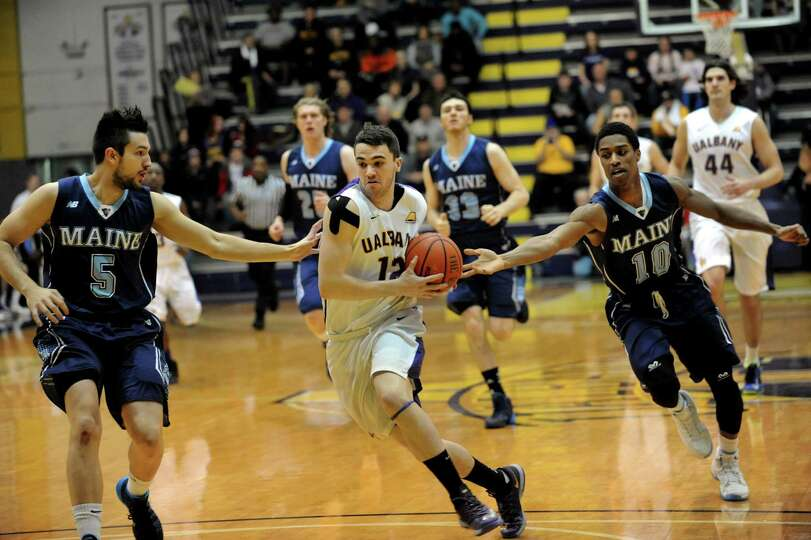 UAlbany's Peter Hooley, center, drives up court as Maine's Zarko Valjarevic, left, and Shaun Lawton