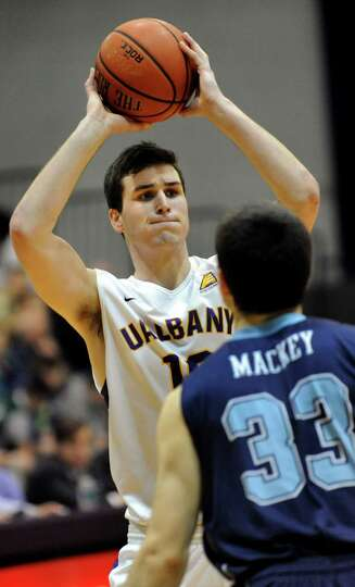 UAlbany's Mike Rowley, left, looks to pass as Maine's Ethan Mackey defends during their basketball g
