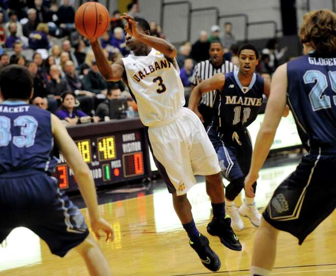 UAlbany's DJ Evans, center, passes the ball during their basketball game against Maine on Saturday,