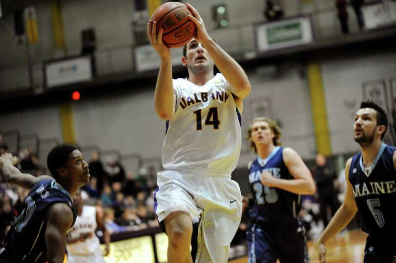 UAlbany's Sam Rowley, center, goes to the hoop during their basketball game against Maine on Saturda