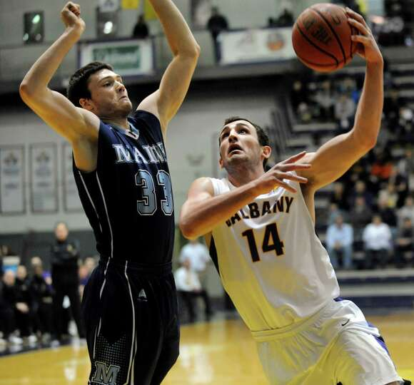 UAlbany's Sam Rowley, right, goes to the hoop as Maine's Ethan Mackey defends during their basketbal