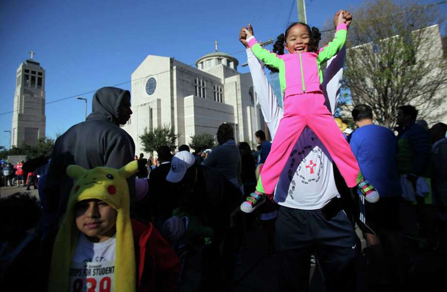 Jazmine Constantine, 5, plays with her father John Constantine, Jr. right before starting the David K. Guite Memorial 1K Family Fun Run at Co-Cathedral of the Sacred Heart on Saturday, Feb. 15, 2014, in Houston. Photo: Mayra Beltran, Houston Chronicle / © 2014 Houston Chronicle
