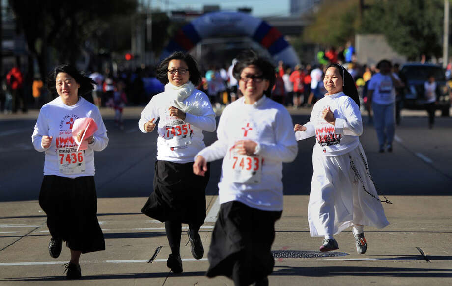 Sister Teresa Paul, on right, joins walkers and runners participating in the 9th Annual Steps for Students David K. Guite Memorial 1K Family Fun Run at Co-Cathedral of the Sacred Heart on Saturday, Feb. 15, 2014, in Houston. Photo: Mayra Beltran, Houston Chronicle / © 2014 Houston Chronicle