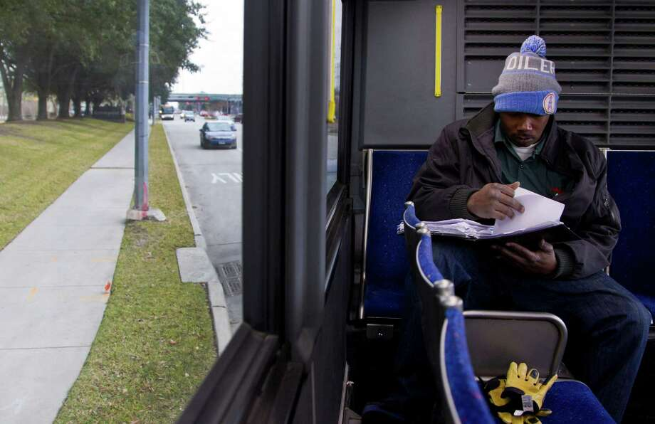 Jerome Edmond, a 34-year-old Army veteran, checks his homework as he rides his third bus before a mile hike to campus. Photo: Karen Warren, Staff / © 2013 Houston Chronicle