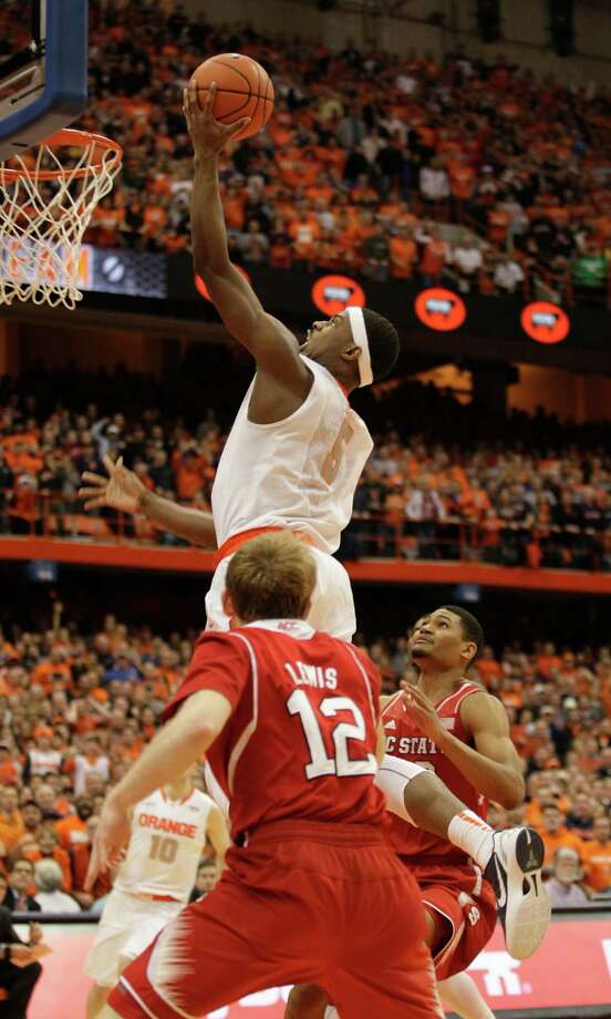 CORRECTS TO SECOND HALF, INSTEAD OF FIRST - Syracuse's C.J. Fair, top, shoots what became the winning basket against North Carolina State in the second half of an NCAA college basketball game in Syracuse, N.Y., Saturday, Feb. 15, 2014. Goaltending was called against North Carolina State's Ralston Turner on the play. Syracuse won 56-55. (AP Photo/Nick Lisi) ORG XMIT: NYNL104 Photo: Nick Lisi / FR171024 AP