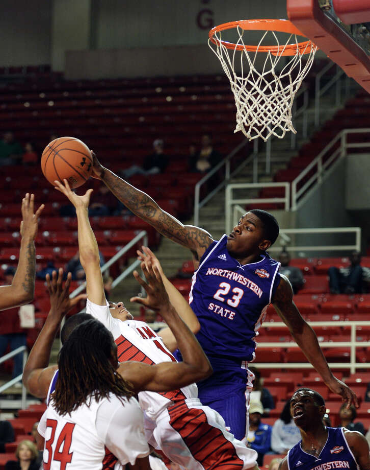 Lamar's Nimrod Hilliard, No. 11, has his shot blocked by Northwestern's Zikiteran Woodley, No. 23, during Saturday night's game. The Lamar University men's basketball team played Northwestern State University at the Montagne Center on Saturday night. Photo taken Saturday, 2/15/14 Jake Daniels/@JakeD_in_SETX Photo: Jake Daniels / ©2013 The Beaumont Enterprise/Jake Daniels