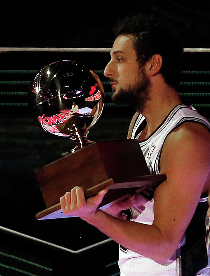 Marco Belinelli of the San Antonio Spurs holds a trophy after he won the three-point contest during the skills competition at the NBA All Star basketball game, Saturday, Feb. 15, 2014, in New Orleans.(AP Photo/Bill Haber) Photo: Bill Haber, Associated Press / FR170136 AP