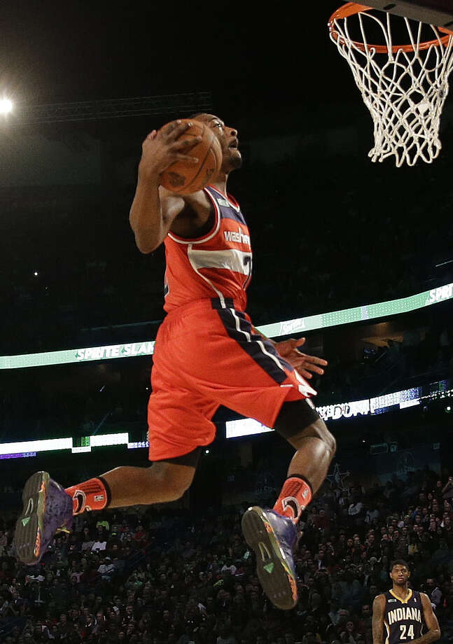 Washington's John Wall soars in the slam dunk contest. Wall teamed with Toronto's Terrence Ross and Indiana's Paul George to win the event for the East, the first time the competition was a team contest between conferences. Photo: Gerald Herbert / Associated Press / AP