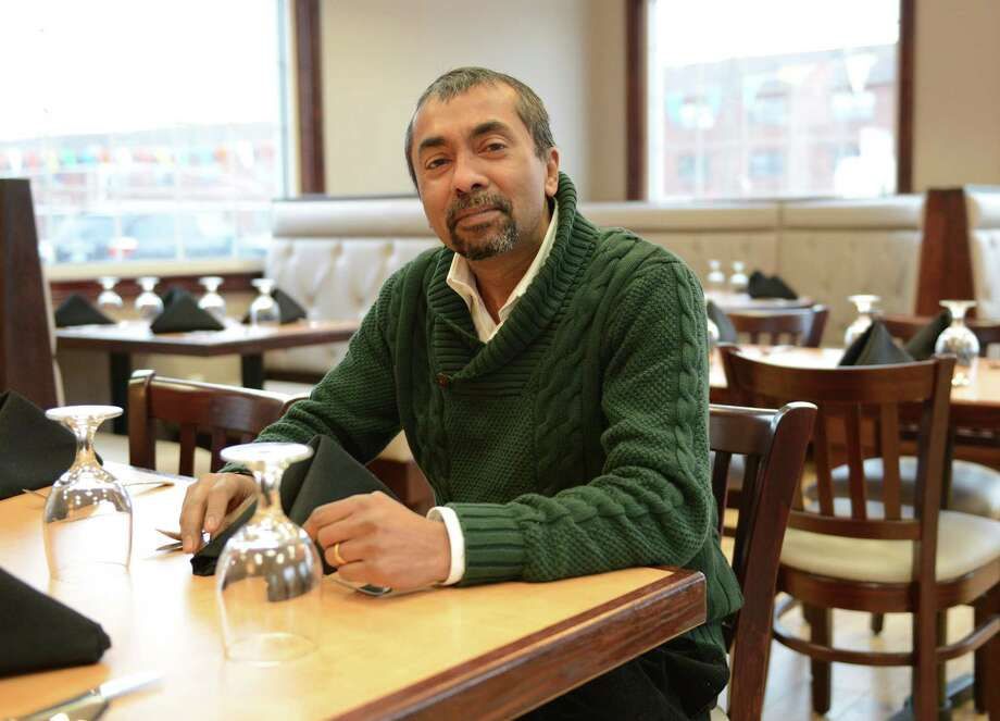 Owner Ahmed Ahsan poses inside Sunrise Fusion in Danbury, Conn. Tuesday, Jan. 28, 2014.  Ahsan owns multiple gas stations, a food market, a staffing agency and now the Sunrise Fusion Halel Chinese restaurant. Photo: Tyler Sizemore / The News-Times