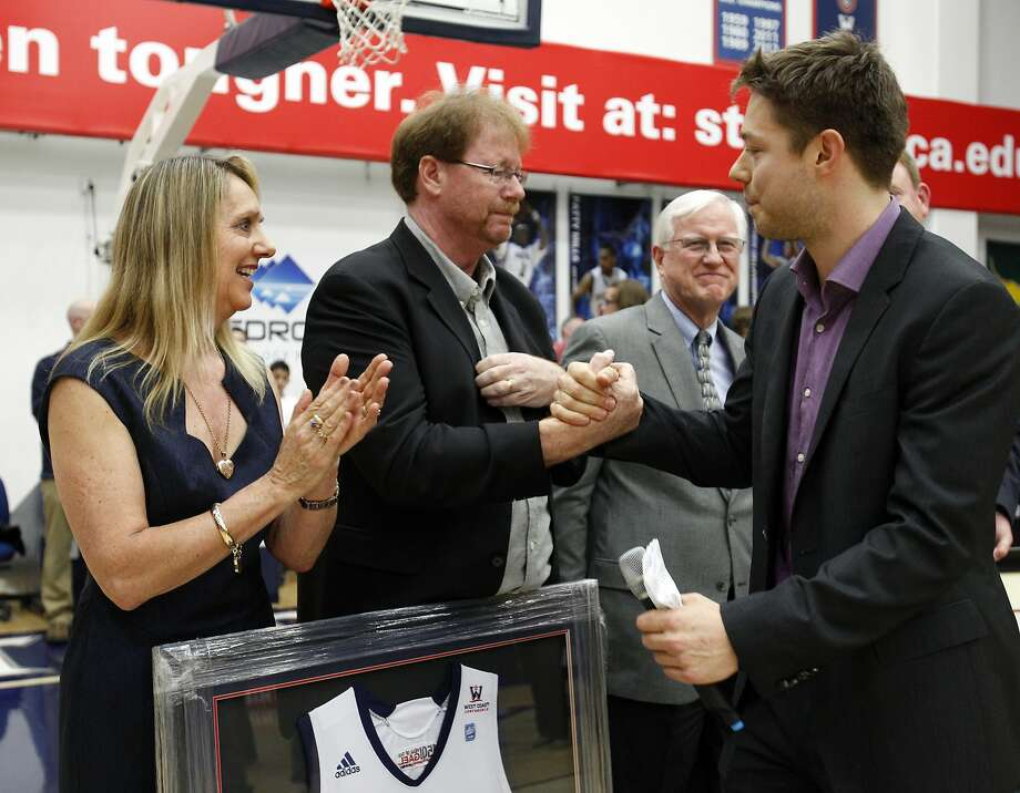 "Former St. Mary's player Matthew Dellavedova (right) had his parents, Leanne and Mark, at Saturday night's ceremony to retire his No. 4 in a pregame ceremony. Dellavedova, a rookie with the Cleveland Cavaliers, finished his career as St. Mary's all-time leader in points, assists, games and three-pointers. During the ceremony, he thanked head coach Randy Bennett as well as Adam Caporn, Daniel Kickert and Patty Mills for building an ""Australian pipeline"" to St. Mary's. For photos from the game, go to  www.sfgate.com/sports. Photo: Carlos Avila Gonzalez, The Chronicle"