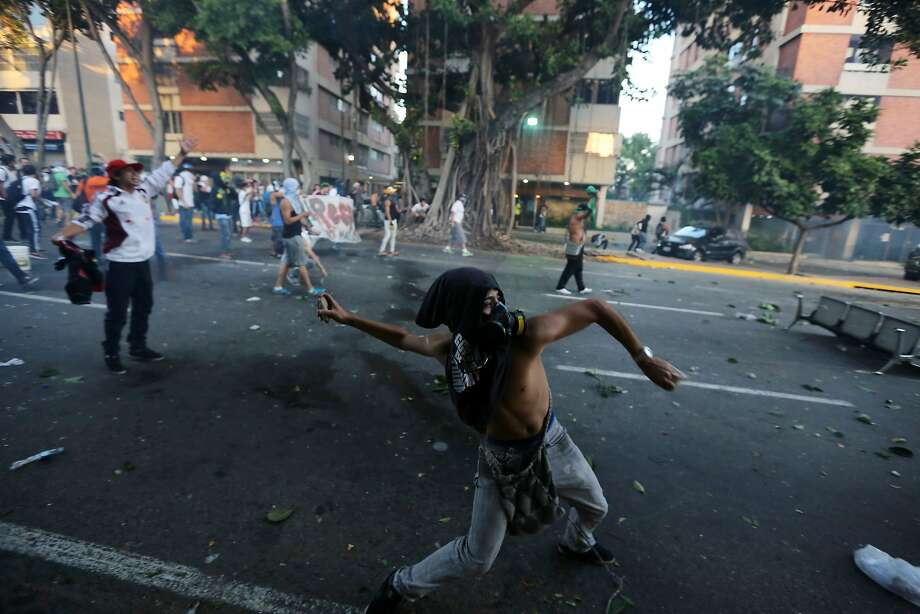 A demonstrator throws stones at the National Bolivarian Police (BNP) after clashes broke out at an opposition protest in Caracas, Venezuela, Saturday, Feb. 15, 2014. Venezuelan security forces backed by water tanks, tear gas and rubber bullets dispersed groups of anti-government demonstrators who tried to block Caracas' main highway Saturday evening. (AP Photo/Fernando Llano) Photo: Fernando Llano, Associated Press