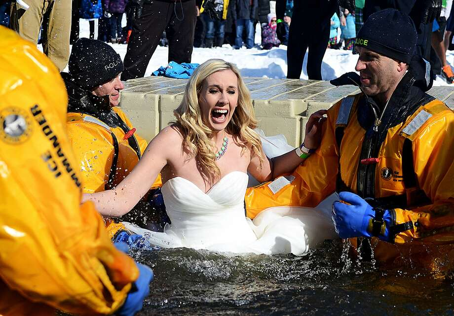 There goes the bride:After taking the plunge into holy matrimony, newlywed Holly Kroeze jumps into frigid Reeds Lake for the Polar Plunge in Grand Rapids, Mich. Photo: Emily Rose Bennett, Associated Press