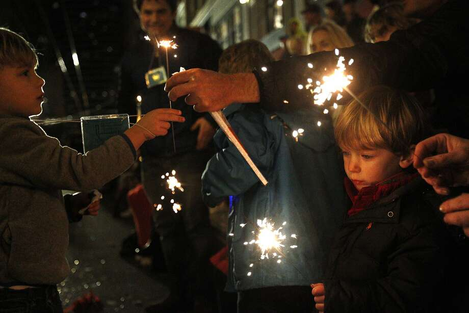 Wyatt Saroyan, 3, right, watches his sparkler as friend Aiden Greenson, 5, left, gets his own as they wait in the stands for the next performance during the annual Chinese New Year Parade Feb. 15, 2014 in downtown San Francisco, Calif. Thousands of people attended the event, which has been celebrated in the city since the 1860's. Photo: Leah Millis, The Chronicle