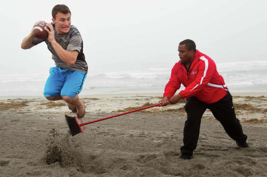 Former Texas A&M quarterback Johnny Manziel leaps over a broom while working out with Hank Speights on Mission Beach in preparation for the National Football League draft Tuesday, Feb. 11, 2014, in San Diego.  ( Brett Coomer / Houston Chronicle ) Photo: Houston Chronicle / © 2014 Houston Chronicle