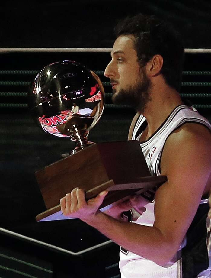 Marco Belinelli of the San Antonio Spurs holds a trophy after he won the three-point contest during the skills competition at the NBA All Star basketball game, Saturday, Feb. 15, 2014, in New Orleans.(AP Photo/Bill Haber) Photo: Associated Press