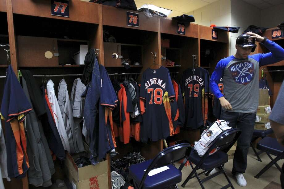 Outfielder George Springer tries on his batting helmet in the clubhouse as pitchers and catchers report to spring training. Photo: Karen Warren, Houston Chronicle