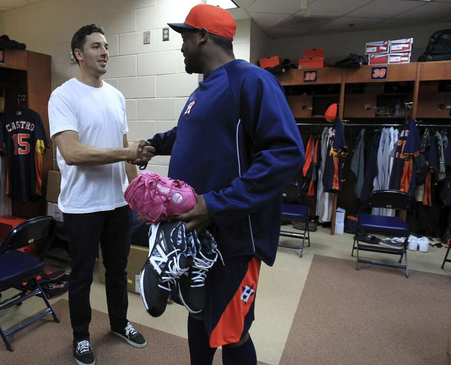 Catcher Jason Castro, left, shakes hands with pitcher Jerome Williams in the clubhouse as pitchers and catchers report to spring training. Photo: Karen Warren, Houston Chronicle
