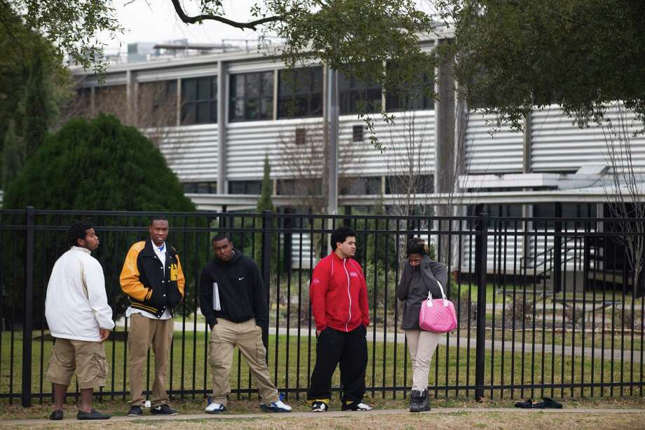 Students stand outside Jesse Jones High School at the end of the school day Thursday, Feb. 6, 2014, in Houston. Jones is one of the schools in the Houston Independent School District to possibly be closed at the end of this year. Photo: Brett Coomer, Houston Chronicle / © 2014 Houston Chronicle