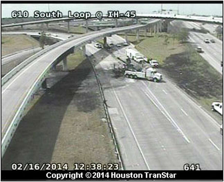 A tow truck removes debris shortly after noon Sunday following a morning tanker-truck wreck that erupted into flames and shut the northbound Gulf Freeway ramp onto eastbound South Loop. (Houston TranStar)