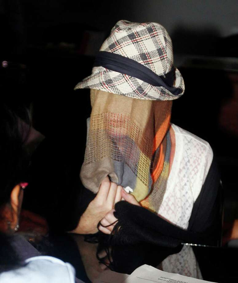 Australian Schapelle Corby, covering her face, listens to an official at the correctional office after she received her parole in Bali, Indonesia, Monday, Feb. 10, 2014. Photo: Firdia Lisnawati, AP  / AP2014