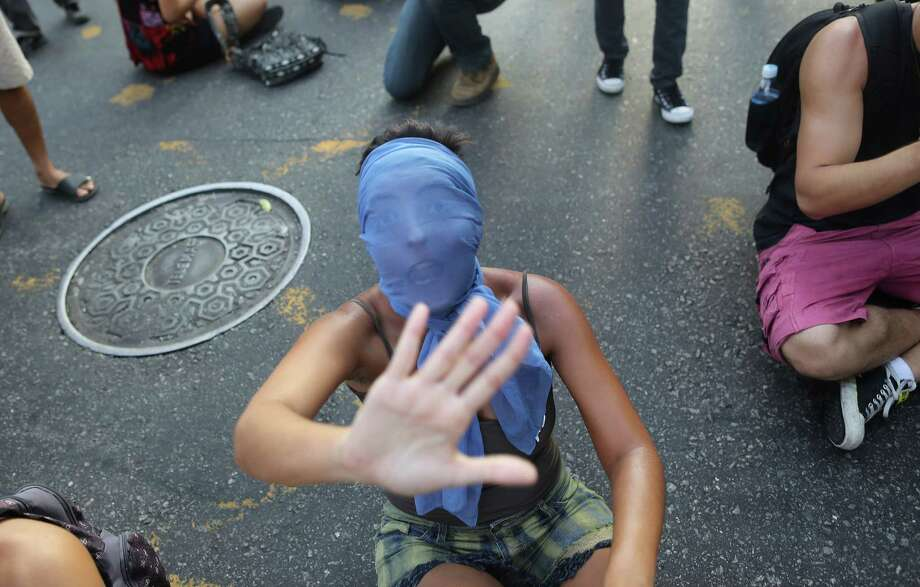 A masked girl shouts while sitting on the street, in protest against the increase on bus fares in Rio de Janeiro, Brazil, Monday, Feb. 10, 2014. Anti-government protests erupted across Brazil last June, hitting their peak as 1 million Brazilians took to streets on a single night, calling for better schools and health care and questioning the billions spent to host this year's World Cup and the 2016 Olympics. The protests have since diminished in size, but remain violent. Photo: Leo Correa, AP  / AP2014