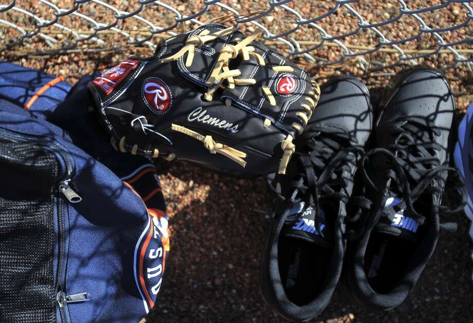 Paul Clemens' glove and shoes sit on the warning track while pitchers and catchers warm up. Photo: Karen Warren, Houston Chronicle