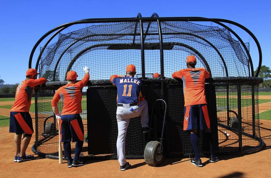 Astros hitting coach John Mallee (11) is surrounded by early-arriving position players Jonathan Villar, far left, Jose Altuve, and Dexter Fowler as he watches them take to the cages. Photo: Karen Warren, Houston Chronicle