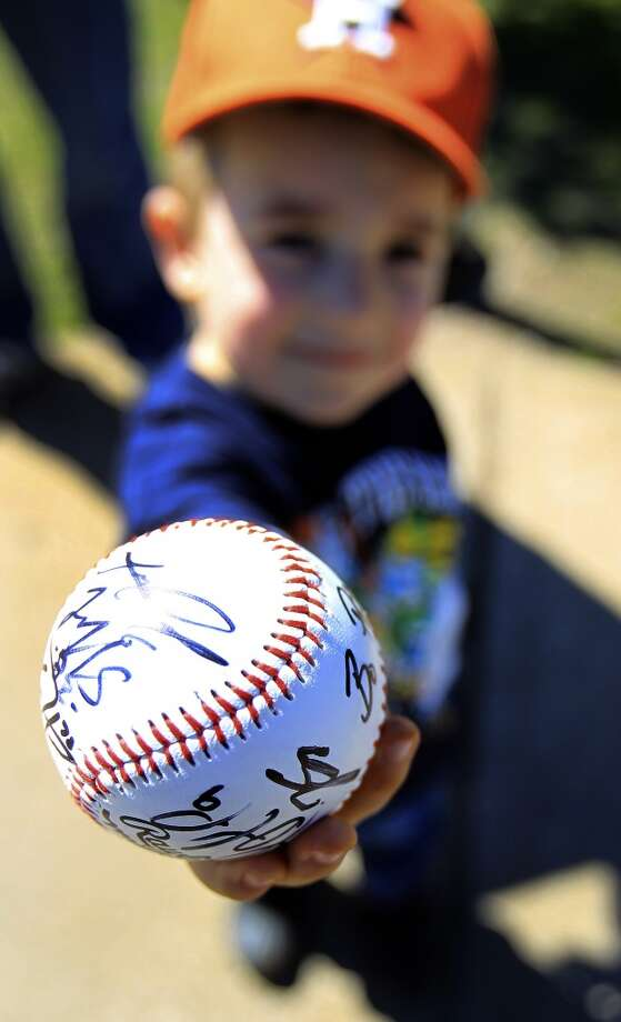 Four-year-old Wyatt Norton, of Kissimmee, holds out a signed ball. Photo: Karen Warren, Houston Chronicle
