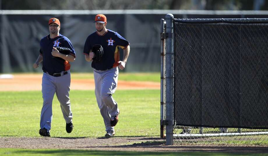 Matt Albers, left, and Scott Feldman (46) run out of a back field during the first day of workouts. Photo: Karen Warren, Houston Chronicle