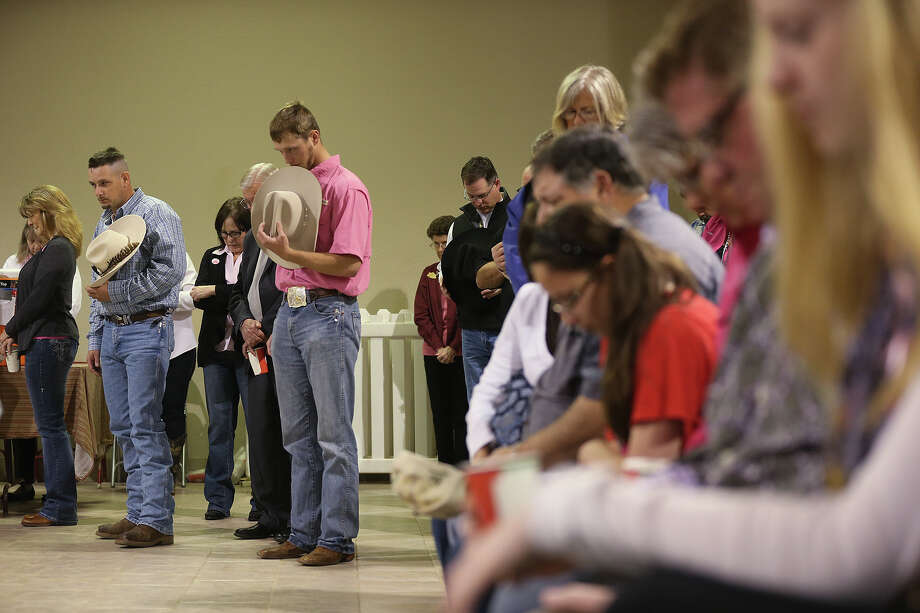 Wesley Walters, left in blue, and Jared Maddox, center in pink, remove their hats during prayer at the at the San Antonio Stock Show and Rodeo Cowboy Church services, Sunday, Feb. 16, 2014. Photo: JERRY LARA, San Antonio Express-News / © 2014 San Antonio Express-News