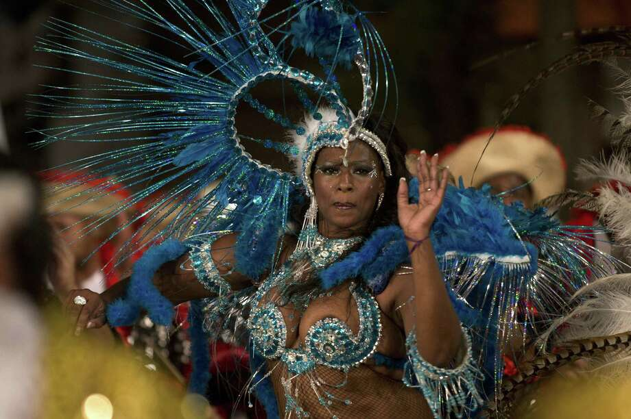 "A dancer performs in a street of the Sur neighbourhood in Montevideo, during the second night of the ""Llamadas"" (Calls) parade on February 14, 2014. The ""Llamadas"" is Uruguay's biggest carnival parade, in which ""comparsas"" -- groups of dancers and drummers of the traditional ""candombe"" music -- compete during two nights of parades.  Photo: PABLO PORCIUNCULA, Getty Images / 2014 AFP"