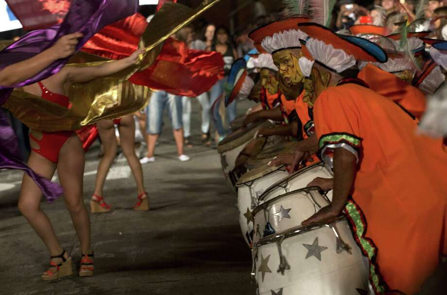 """Dancers and drummers perform along a street of Montevideo's Sur neighbourhood, on the first night of the """"Llamadas"""" (Calls) carnival parade, on February 13, 2014. The """"Llamadas"""" is Uruguay's biggest carnival parade, in which """"comparsas"""" -- group of dancers and drummers of the traditional """"candombe"""" music -- compete in two nights of parades.  Photo: PABLO PORCIUNCULA, Getty Images / 2014 AFP"""