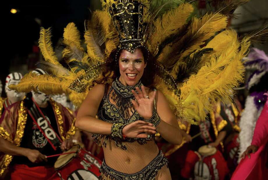 "A dancer performs along a street of Montevideo's Sur neighbourhood, on the first night of the ""Llamadas"" (Calls) carnival parade, on February 13, 2014. The ""Llamadas"" is Uruguay's biggest carnival parade, in which ""comparsas"" -- group of dancers and drummers of the traditional ""candombe"" music -- compete in two nights of parades.  Photo: PABLO PORCIUNCULA, Getty Images / 2014 AFP"