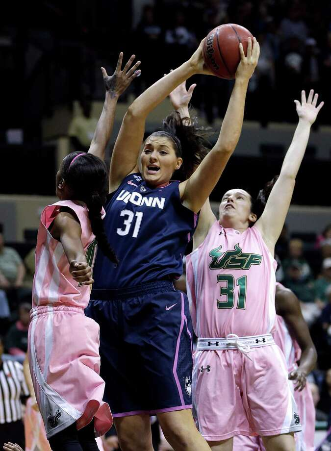 Connecticut center Stefanie Dolson (31, center) grabs a rebound away from South Florida guard Courtney Williams (10) and guard Laura Marcos Canedo (31) during the first half of an NCAA women's college basketball game, Sunday, Feb. 16, 2014, in Tampa, Fla. Photo: Chris O'Meara, AP / Associated Press