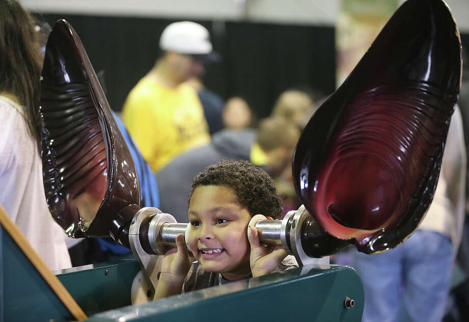 Ezekiel Scott, 7, plays with large bat ears that are part of the San Antonio Stock Show and Rodeo'sBats, Mysteries and Myths exhibit, Sunday, Feb. 16, 2014. Photo: JERRY LARA, San Antonio Express-News / © 2014 San Antonio Express-News