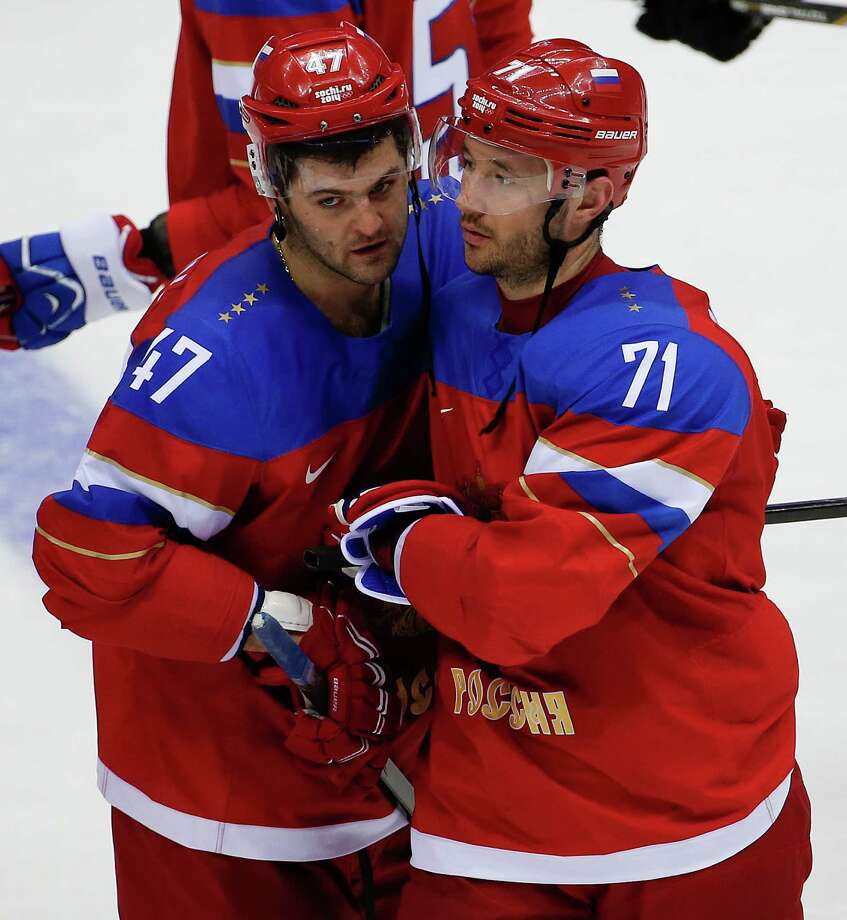 Russia forward Ilya Kovalchuk, right, is congratulated by Russia forward Alexander Radulov after hitting the winning shot in a shootout against Slovakia during a men's ice hockey game at the 2014 Winter Olympics, Sunday, Feb. 16, 2014, in Sochi, Russia. Russia won 1-0.  (AP Photo/Julio Cortez) ORG XMIT: OLYMH173 Photo: Julio Cortez / AP
