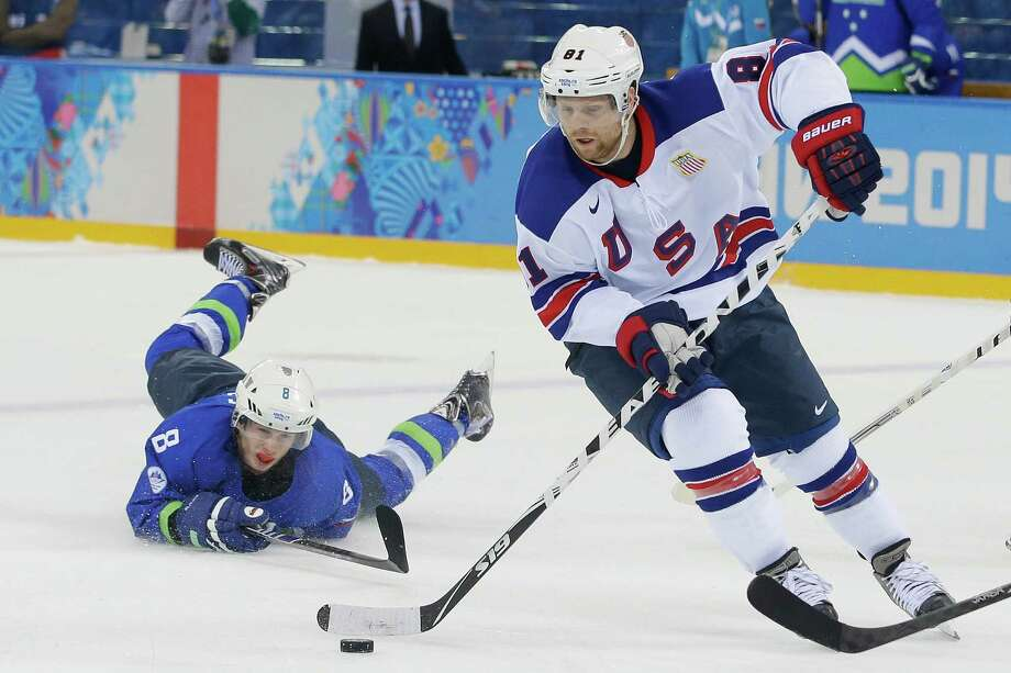 USA forward Phil Kessel take the puck away from Slovenia forward Ziga Jeglic during the 2014 Winter Olympics men's ice hockey game at Shayba Arena Sunday, Feb. 16, 2014, in Sochi, Russia. (AP Photo/Matt Slocum) ORG XMIT: OLYMH216 Photo: Matt Slocum / AP
