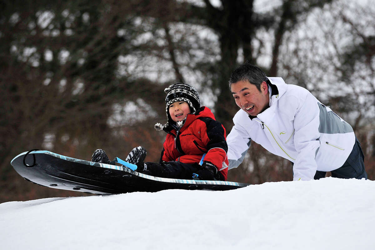 Kenichi Shimamura gives his son, Nozomi, a push down a hill at the West Greenwich Civic Center Park in Greenwich, Conn., on Sunday, Feb. 16, 2014.