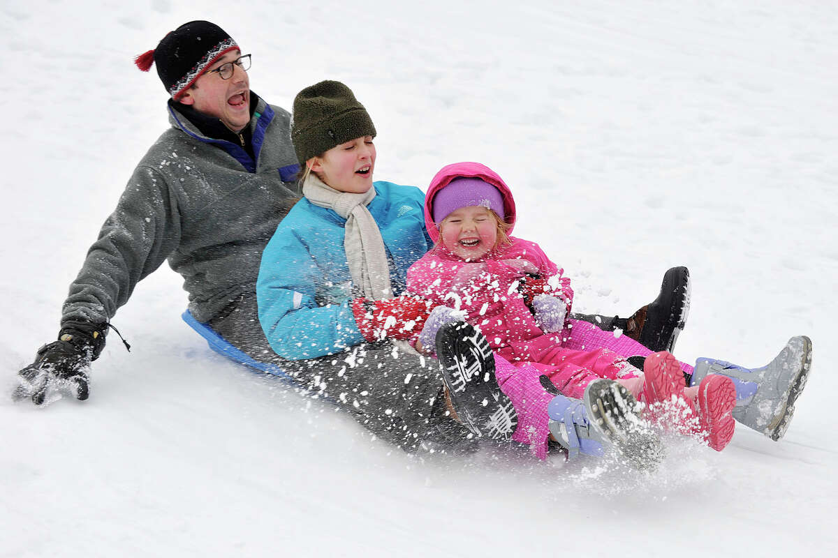 From left, John Straus, Lili Beecher and Tatum Nelson sled down a hill in the park outside Julian Curtiss School in Greenwich, Conn., on Sunday, Feb. 16, 2014.
