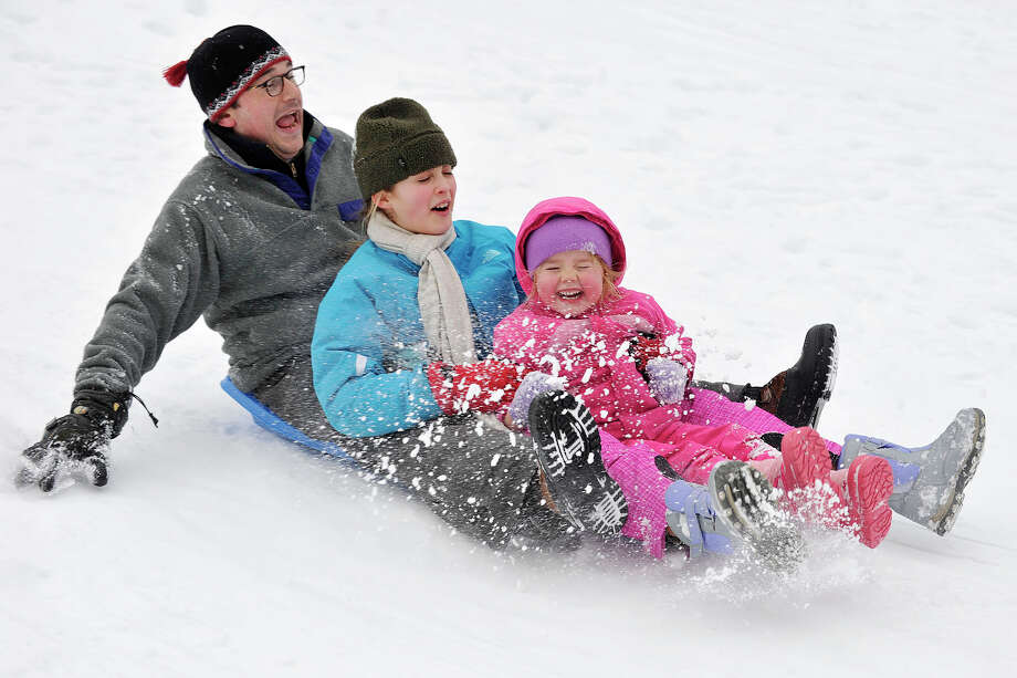 From left, John Straus, Lili Beecher and Tatum Nelson sled down a hill in the park outside Julian Curtiss School in Greenwich, Conn., on Sunday, Feb. 16, 2014. Photo: Jason Rearick / Stamford Advocate
