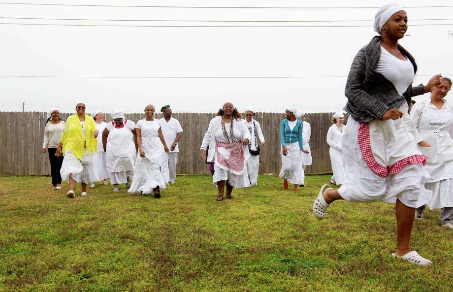 A group of worshipers make their way back to cook, clean and prepare for another ceremony after an eggun or ancestral ceremony practiced during day-long Santeria religious ceremonies at a Houston home Sunday, Feb. 9, 2014. Dr. Faizah Perry, a priestess of the deity Ogun, estimates there are more than 1,000 people in the Houston area that practice the Santeria religion. Santeria, also known as Lucumí, is an African-Caribbean religion based on Yoruba beliefs and traditions including the worship of Yoruba deities with some Roman Catholic elements added. Photo: Johnny Hanson, Houston Chronicle / © 2014  Houston Chronicle