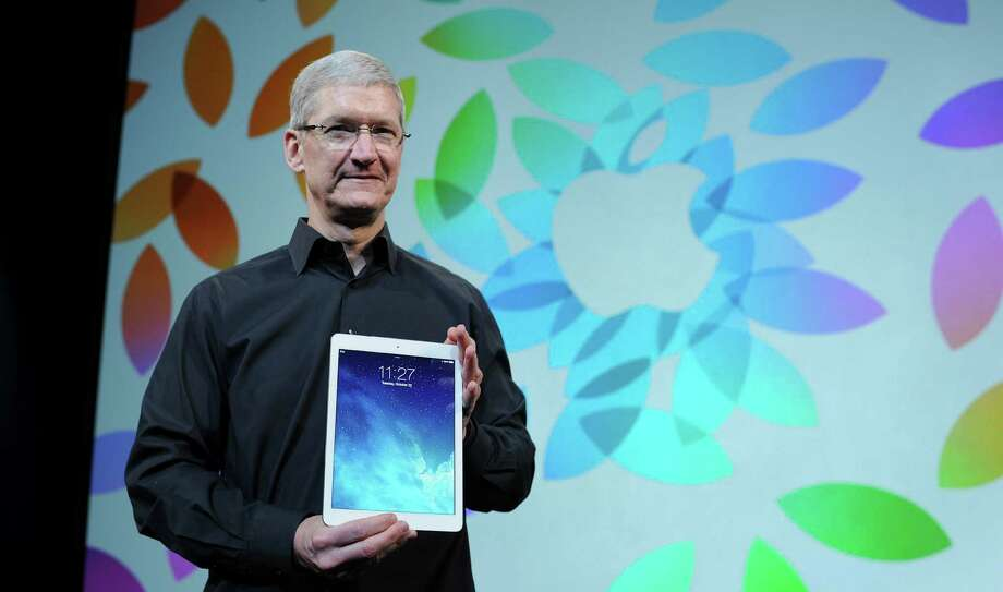 Apple CEO Tim Cook, holding up an iPad Air, appears to be moving the company away from the world of consumer electronics and into the world of automobiles and medical devices. Photo: Noah Berger / Bloomberg / © 2013 Bloomberg Finance LP