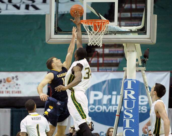 Billy Baron, left, of Canisius has his shot blocked by Imoh Silas of Siena during the Siena and Cani